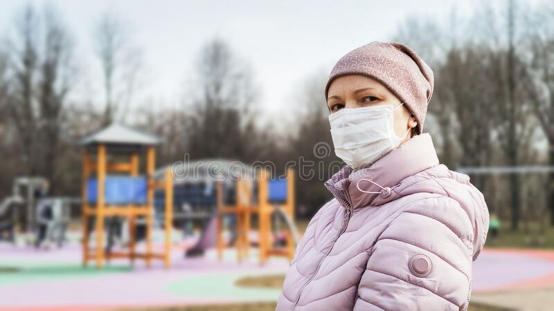 Woman at playground with surgical mask on face during COVID-19 coronavirus pandemic stock photos