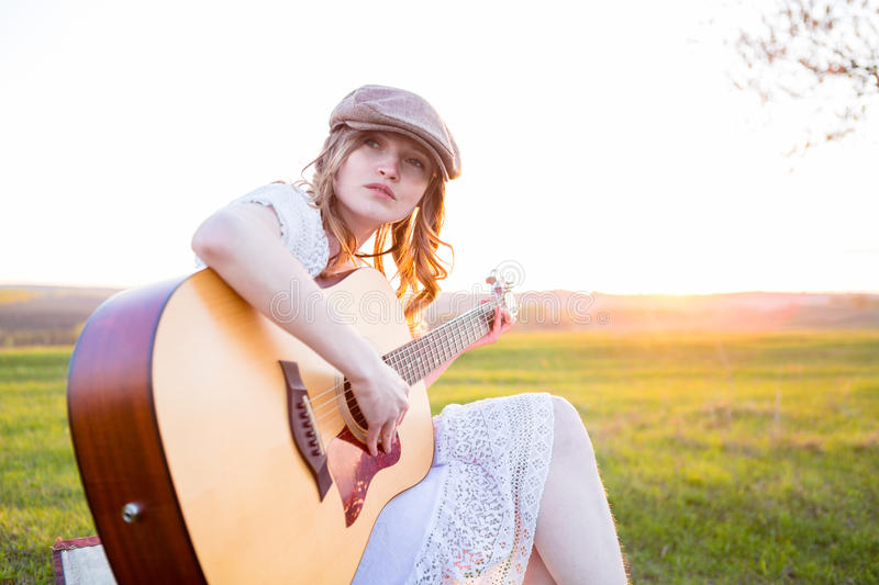 Woman playing acoustic guitar in park stock photos