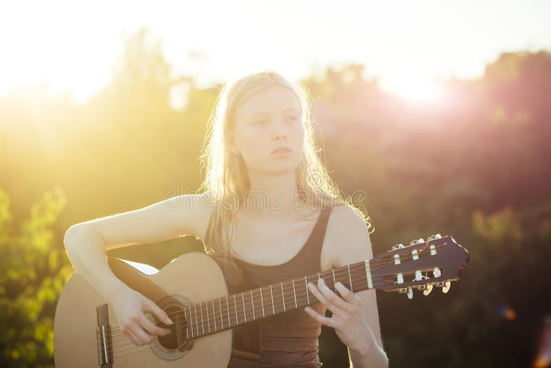 Woman playing acoustic guitar in summer park outdoor.  royalty free stock photos