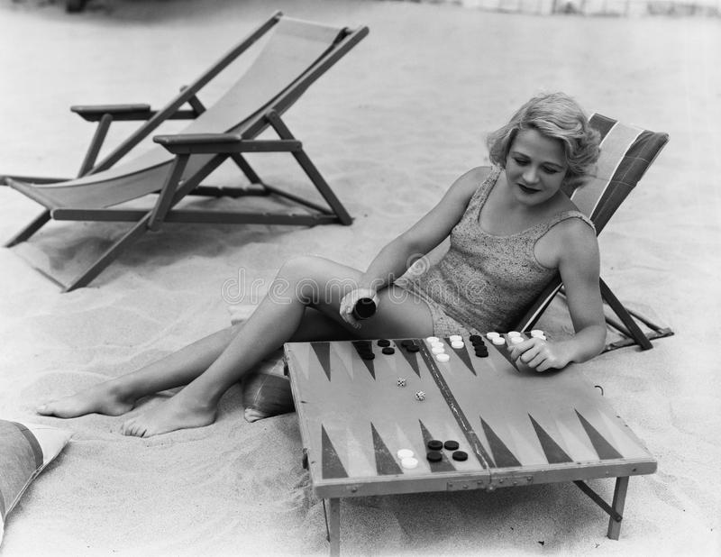Woman playing backgammon on beach stock photos