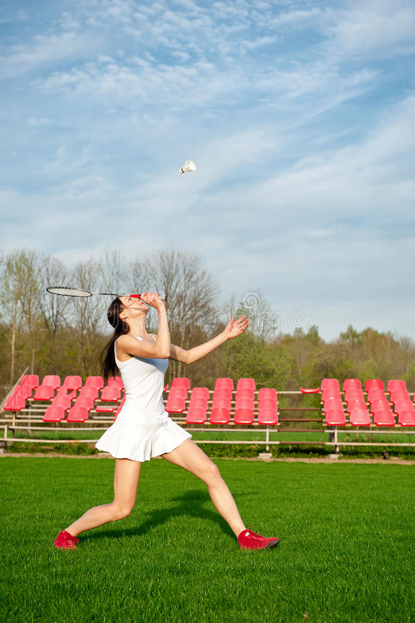Woman playing badminton game in the park. Sport theme shot stock photo