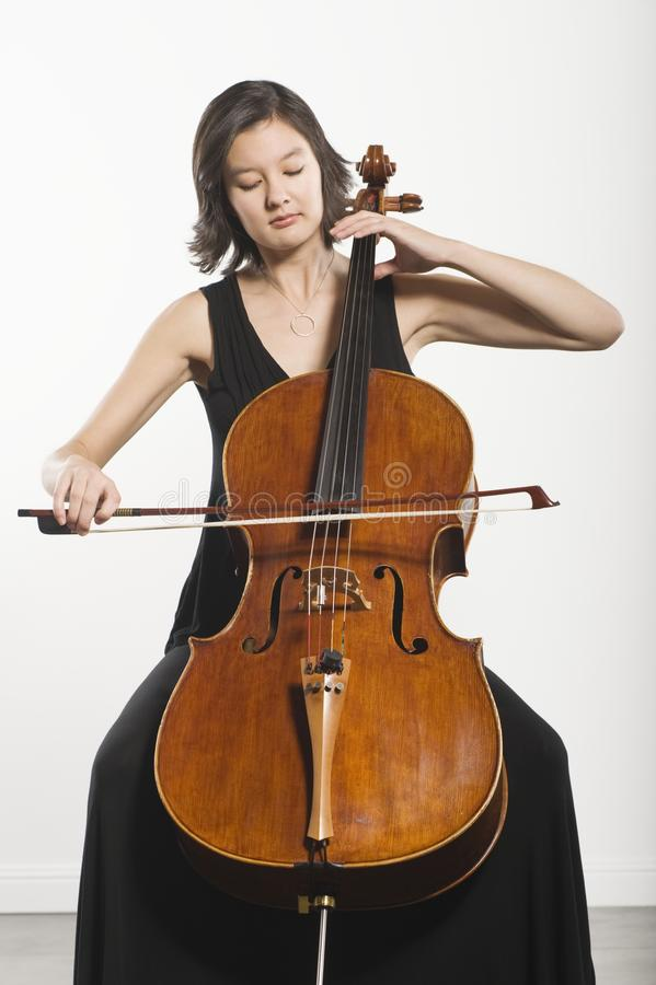 Woman Playing Cello. Beautiful young woman playing cello classical music instrument royalty free stock images