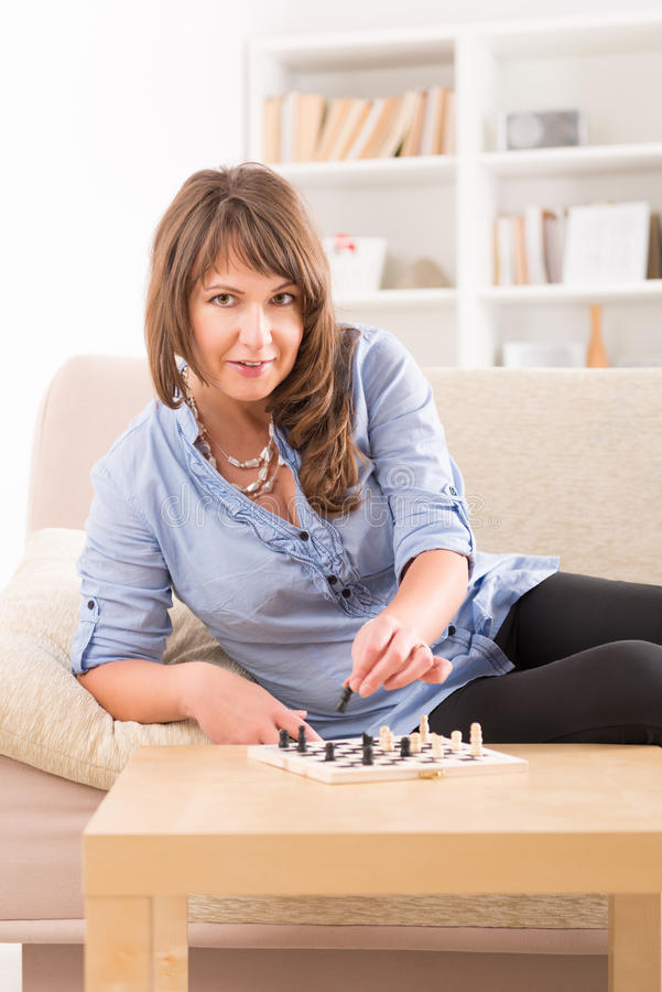 Woman playing chess at home stock photography