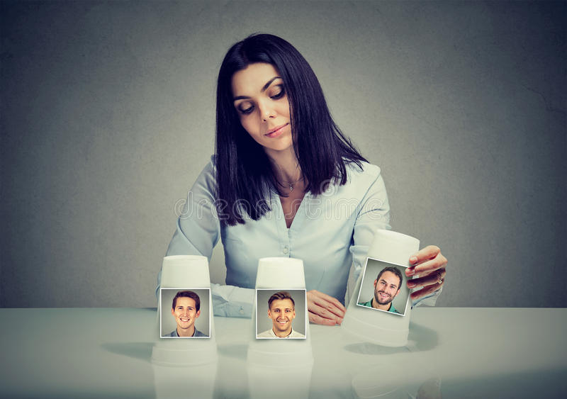 Woman playing a conjuring trick game making a boyfriend choice. Speed dating concept. Woman playing a conjuring trick game making a boyfriend choice royalty free stock photo