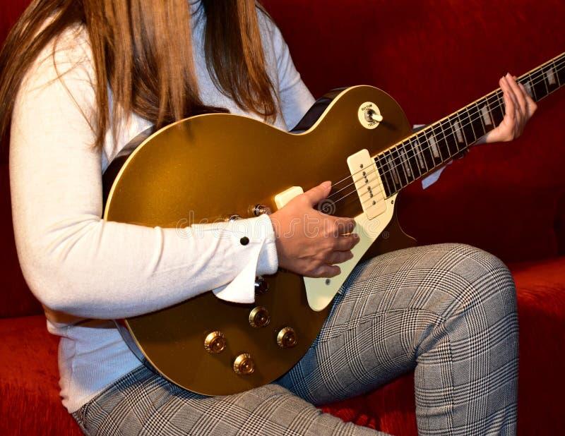 Woman playing a electric guitar. Closeup, no face. stock photos