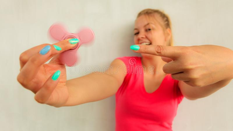 Woman playing fidget spinner stock images