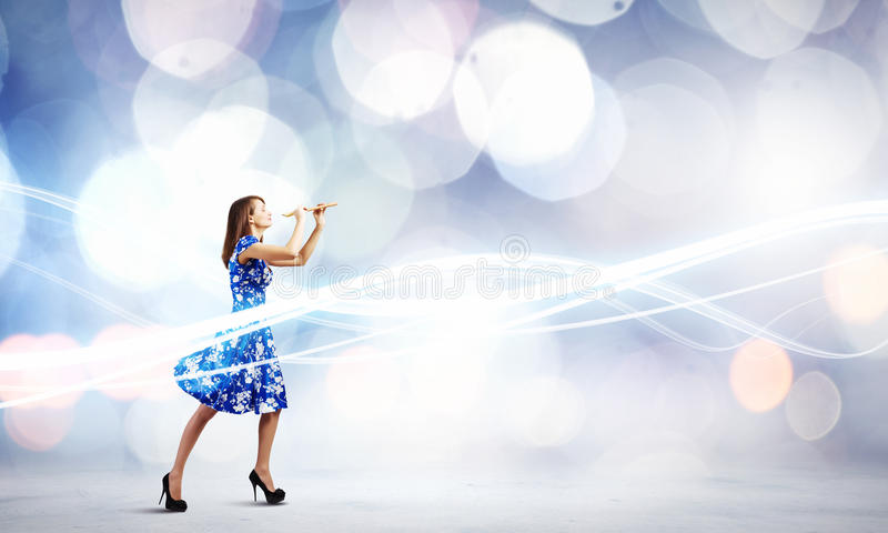 Woman playing fife. Young woman in blue dress playing fife against bokeh background stock photography