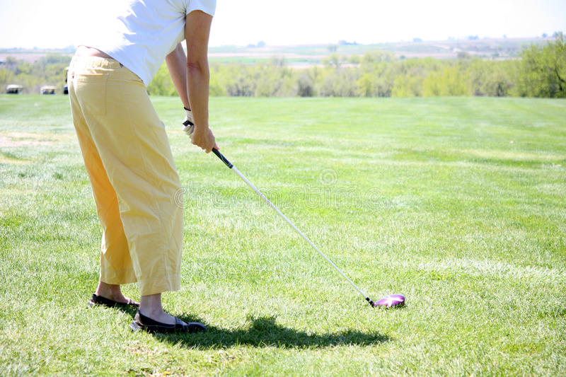 Woman playing golf driving the ball stock photos