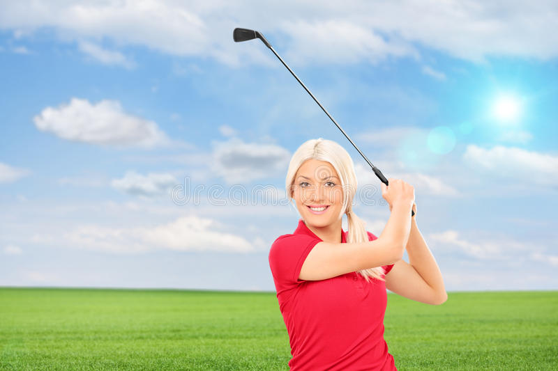 Woman playing golf in a field royalty free stock image