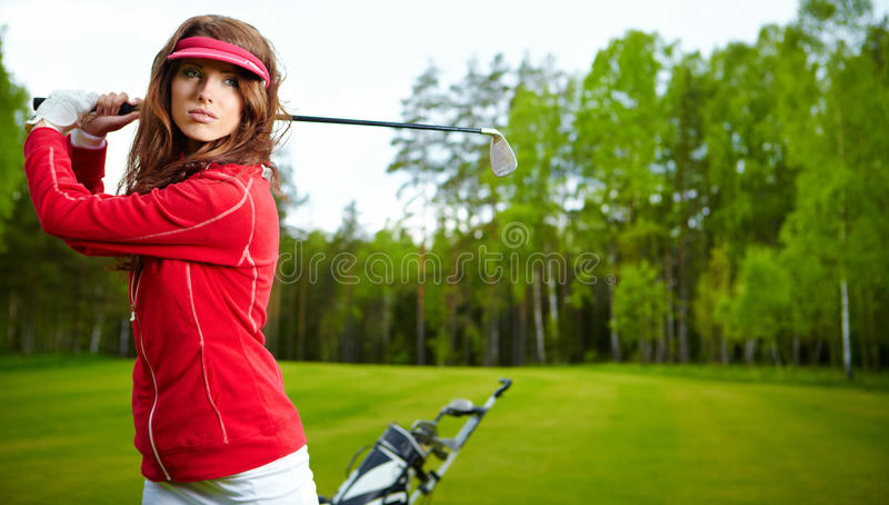 Woman playing golf on a green. Portrait of an woman playing golf on a green stock image