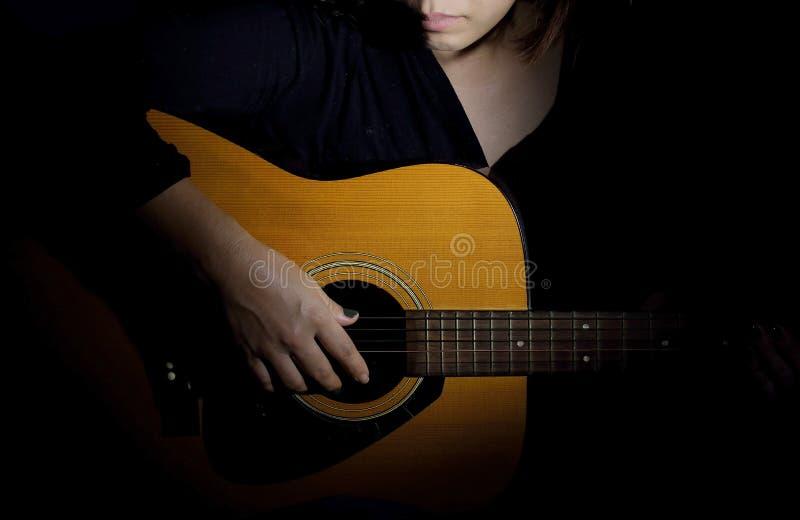 A woman Playing guitar. An asian woman Playing guitar royalty free stock photography