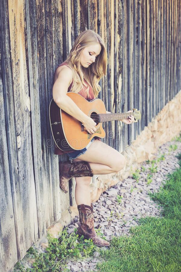 Woman Playing Guitar While Leaning on Wood during Daytime royalty free stock image