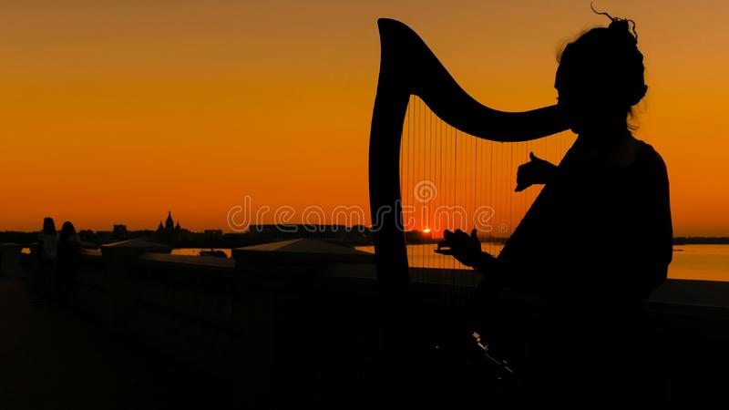 Woman playing harp at sunset royalty free stock images