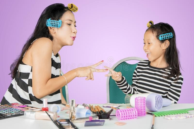 Woman playing with her child after doing makeup royalty free stock images
