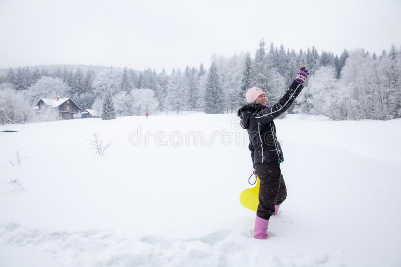 Woman playing with her dog on snow in winter. taking pictures by phone selfie. Young woman playing with her black small dog on snow in winter. taking pictures by royalty free stock photos