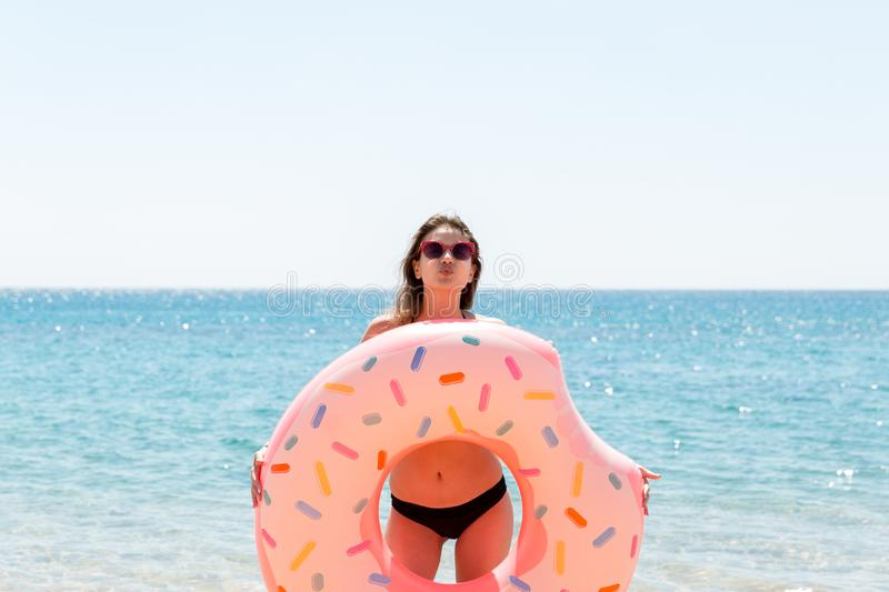 Woman playing with inflatable ring. Girl relaxing on pink inflatable on the beach. Summer holidays and vacation concept on a royalty free stock images