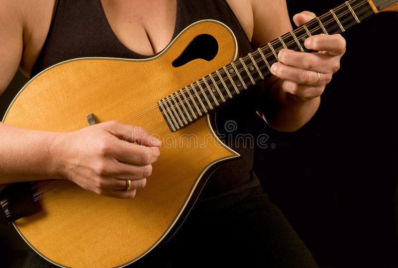 Woman playing mandolin. Close up of woman playing the mandolin, against black stock images