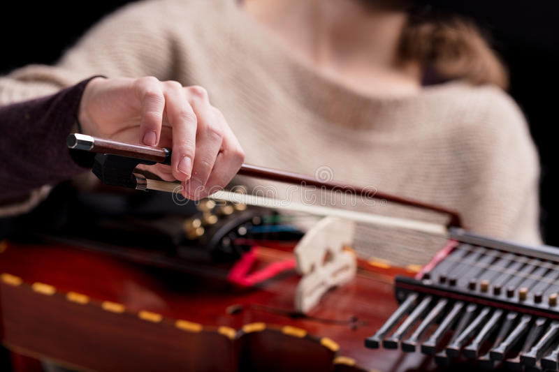 Woman playing a nyckelharpa musical instrument. Woman playing an ancient medieval musical instrument, modern reconstruction of an antique nyckelharpa, often used royalty free stock image