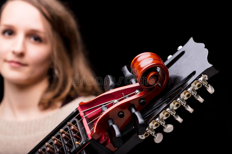 Woman playing a nyckelharpa musical instrument. Woman playing an ancient medieval musical instrument, modern reconstruction of an antique nyckelharpa, often used stock images