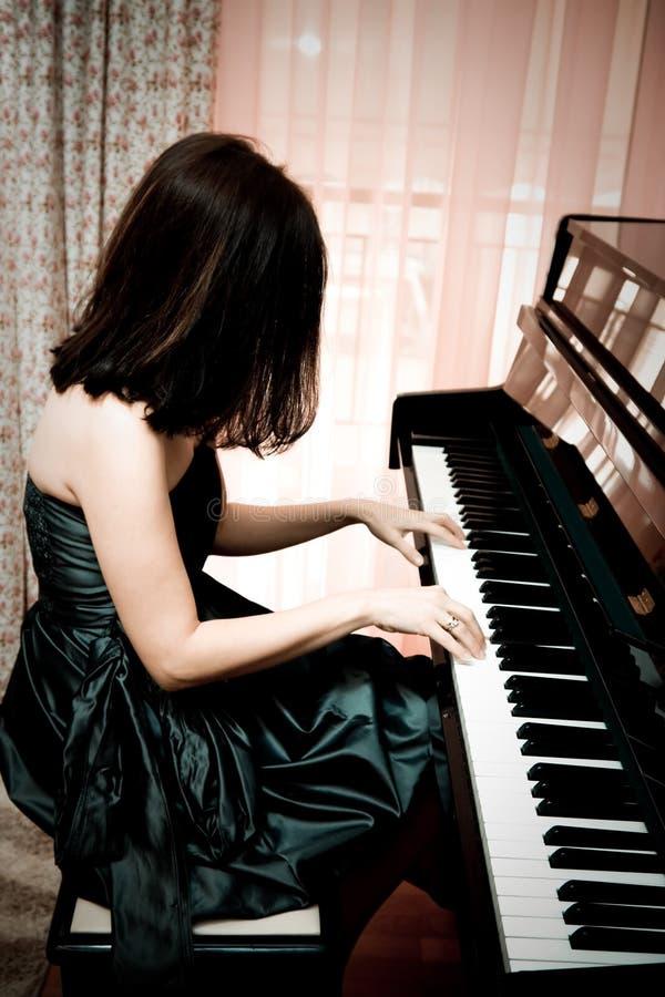 Woman playing piano stock image
