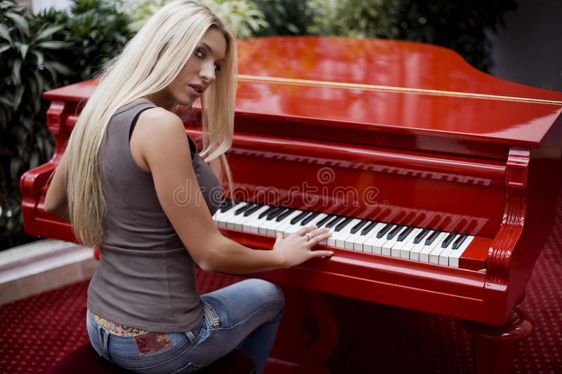 Woman playing the piano. Beautiful woman playing the piano royalty free stock photography
