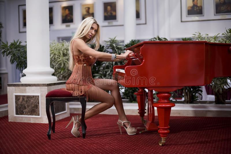 Woman playing the piano. Beautiful luxury woman playing the piano stock image