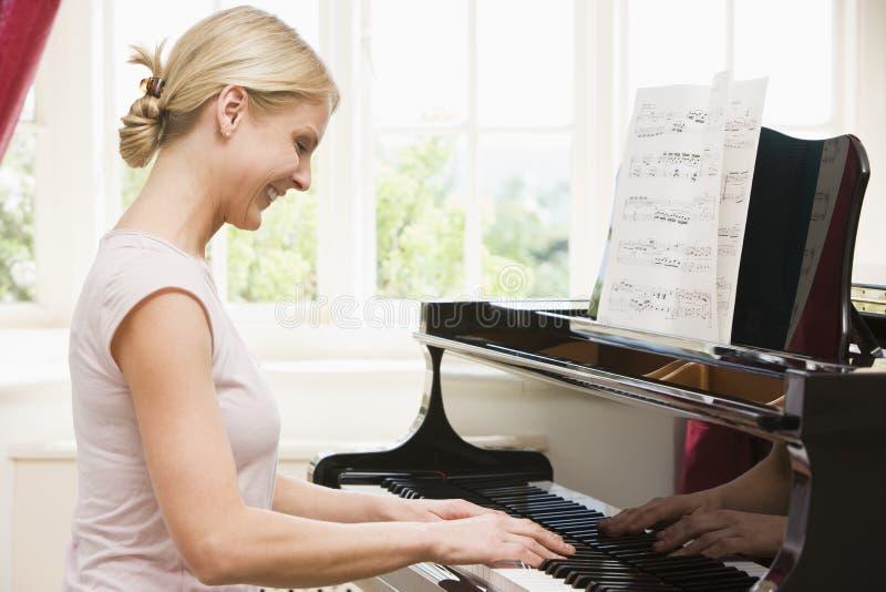 Woman playing piano stock photo