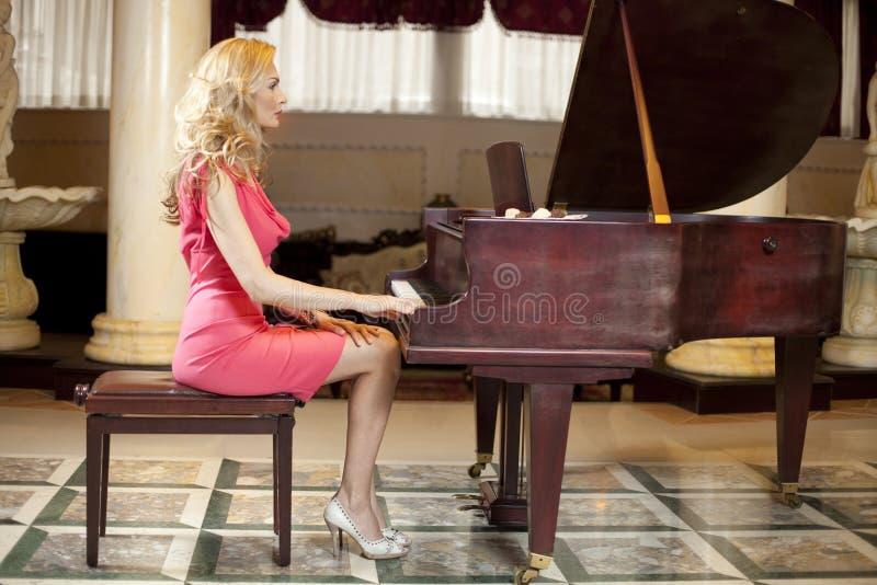 Woman Playing Piano. The Beutiful woman Playing Piano stock photography