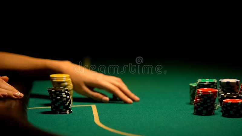 Woman playing poker, chips lying on green table, illegal casino for VIP-clients. Stock photo royalty free stock photo