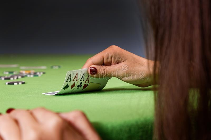 Woman playing poker game and looking at cards. Green table, chips and four aces cards in hand. stock photo