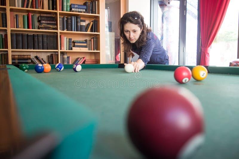 Woman playing pool stock photos
