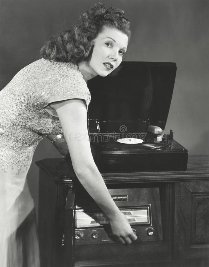 Woman playing record album on phonograph stock photos