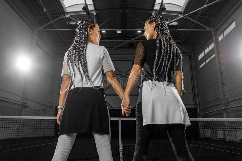 Woman tennis player posing like a fitness fashion model on tennis court. Lesbian couple holding hands on LGBT sport royalty free stock photography
