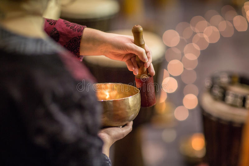 Woman playing on a tibetian singing bowl. Shallow DOF; color toned image stock image