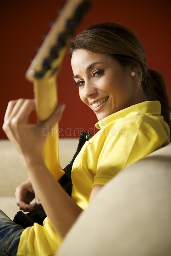 Woman playing and training with electric guitar at home stock image