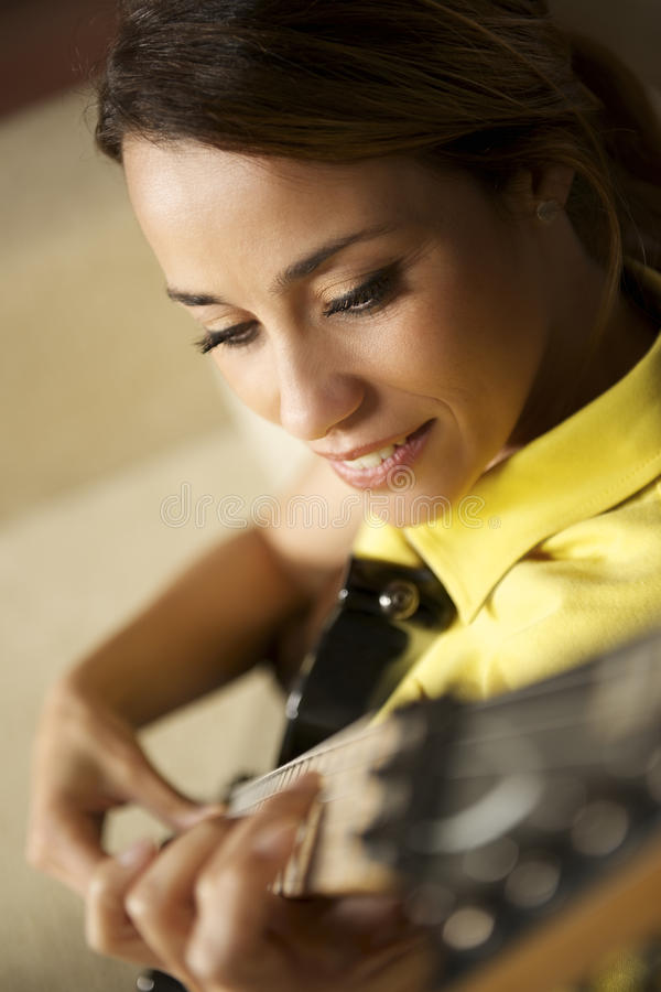 Woman playing and training with electric guitar at home stock photography