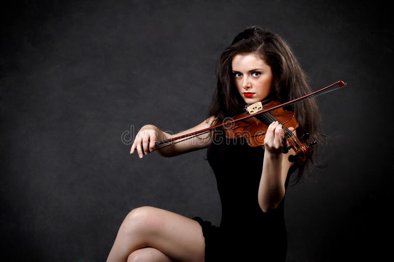 Woman playing violin. Young woman playing violin on dark background royalty free stock image