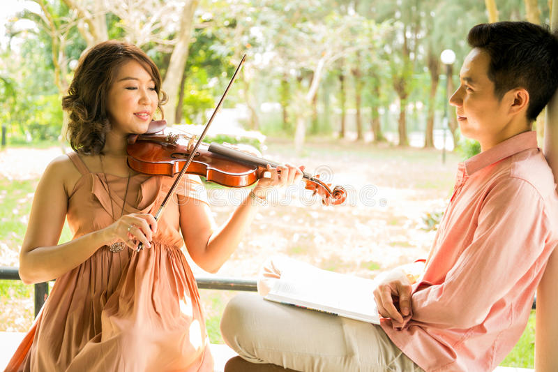 Woman playing violin with her boyfriend royalty free stock photography