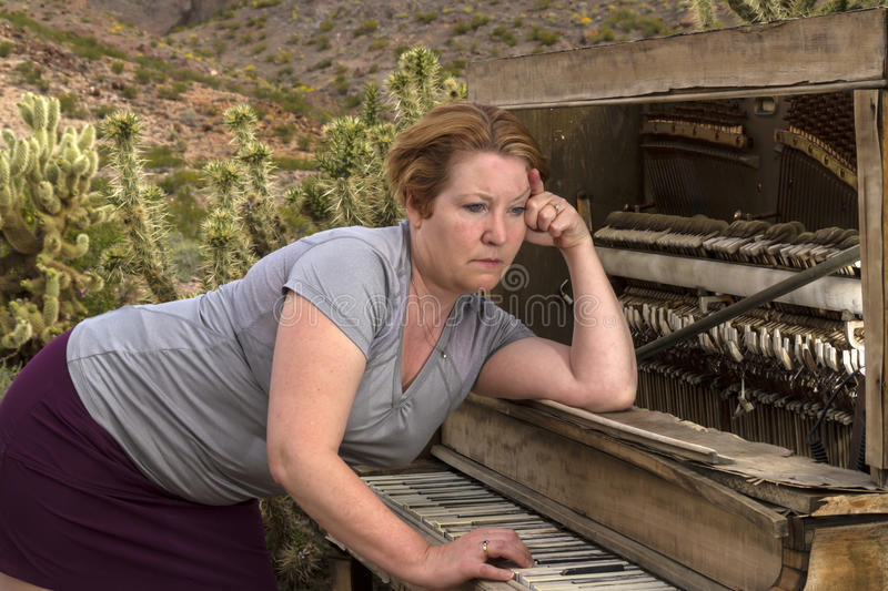 Woman Playing Wooden Piano in Desert, Contemplative Expression. Mature woman in desert setting playing a wooden, antique piano with a sad, contemplative stock photos