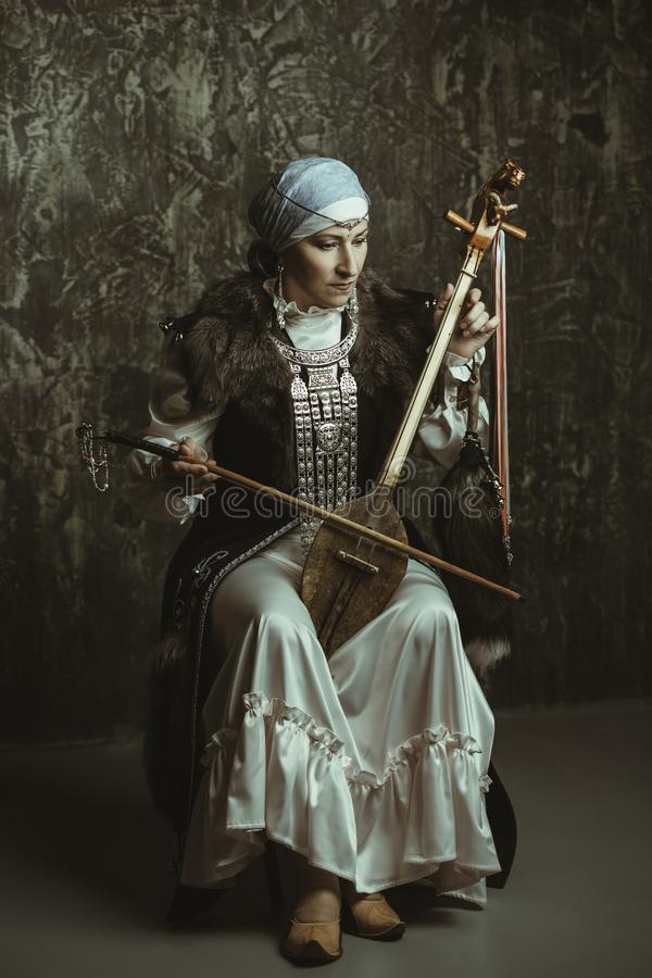 Woman plays ancient violin stock photo