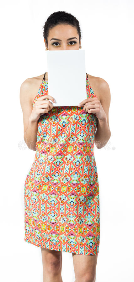 Woman plays with blank card and covers part of the face. She wears a colorful dress. Summer.. stock photos