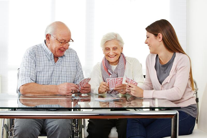 Woman plays cards with senior citizens in nursing home royalty free stock photography