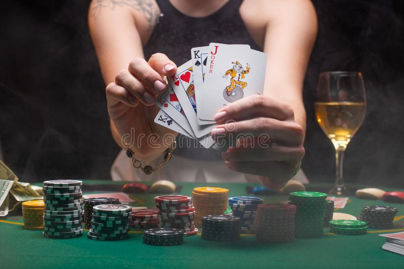 A woman plays in a casino. shows a winning combination on cards. Winning poker.  royalty free stock photo