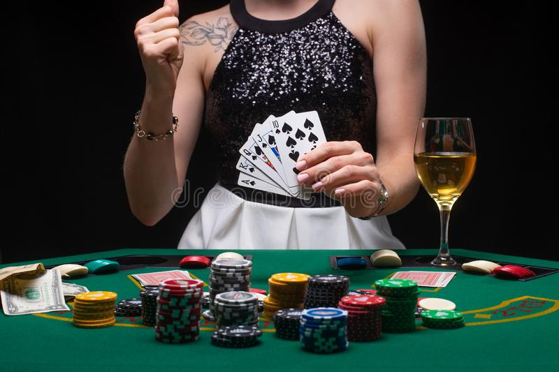 A woman plays in a casino. shows a winning combination on cards. Winning poker.  royalty free stock images