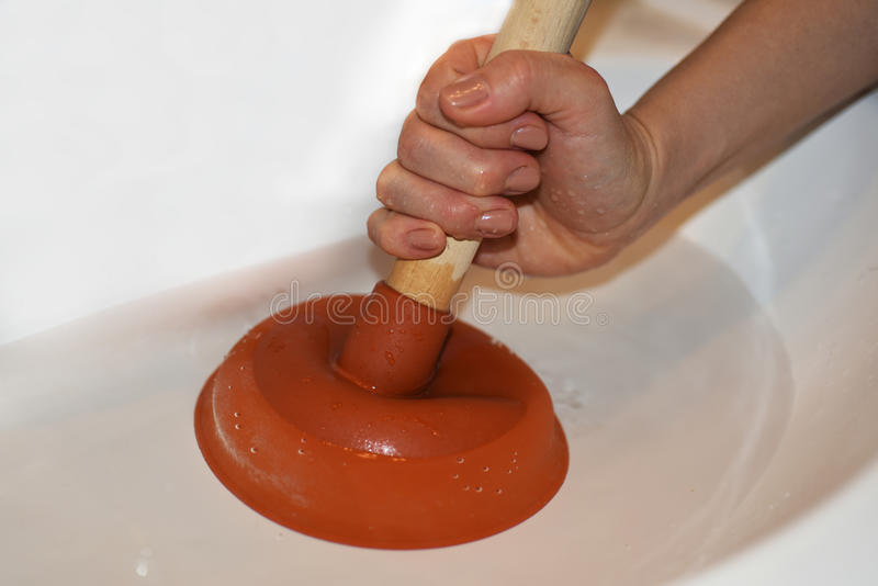 Woman with plunger trying to remove clogged sinks. Abstract photo royalty free stock images