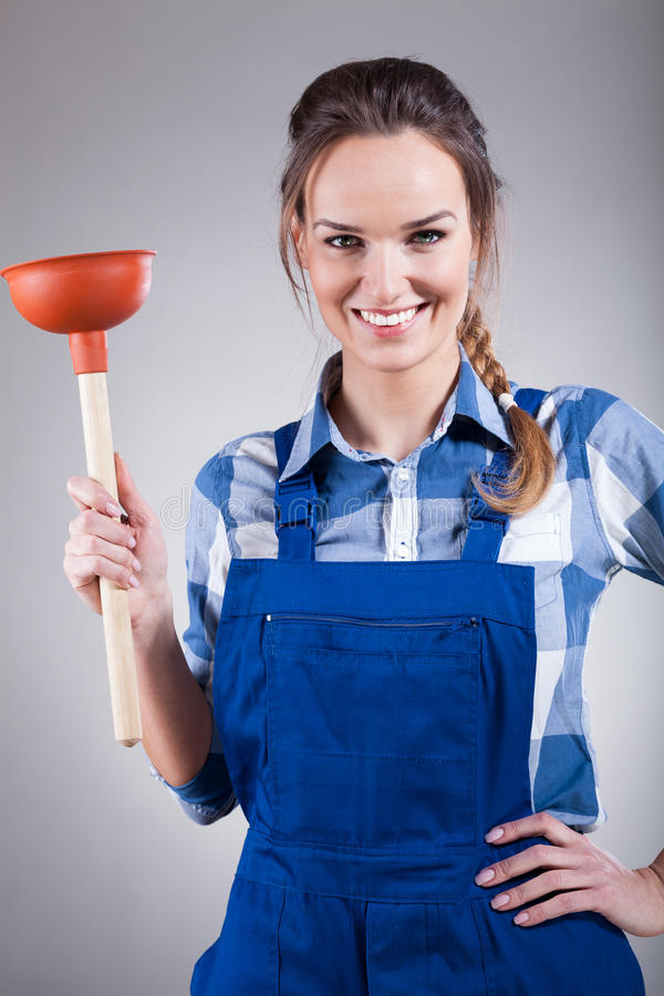 Woman with a plunger. Woman in work clothes holding a plunger royalty free stock image
