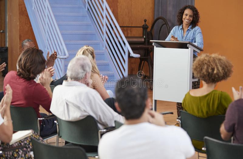 Woman At Podium Chairing Neighborhood Meeting In Community Centre royalty free stock images
