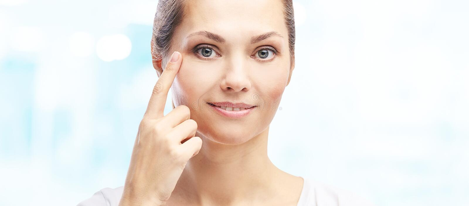 Woman point at dermatology skin problem. Cosmetology beauty girl portrait. Face care procedure royalty free stock images