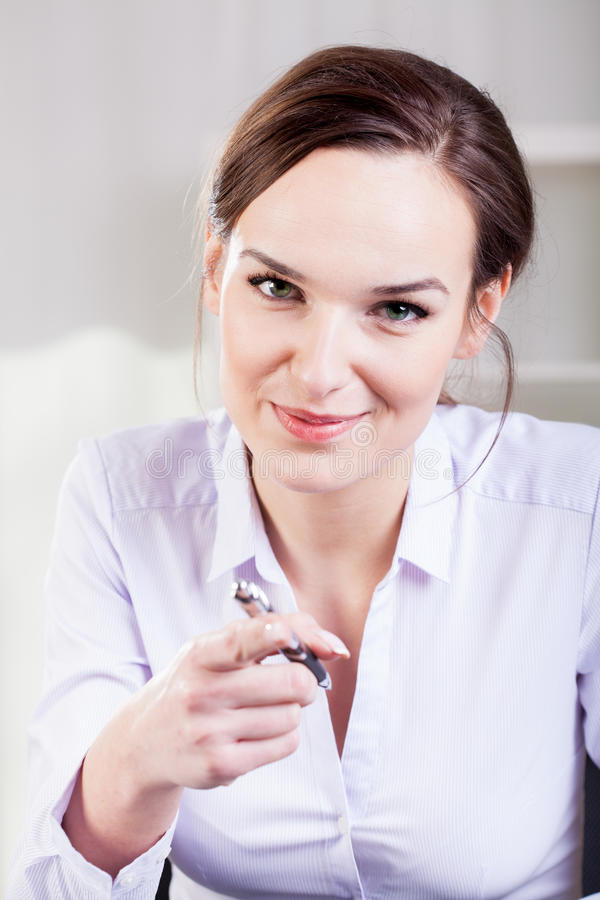 Woman pointing with a ballpen. In a one direction royalty free stock photos