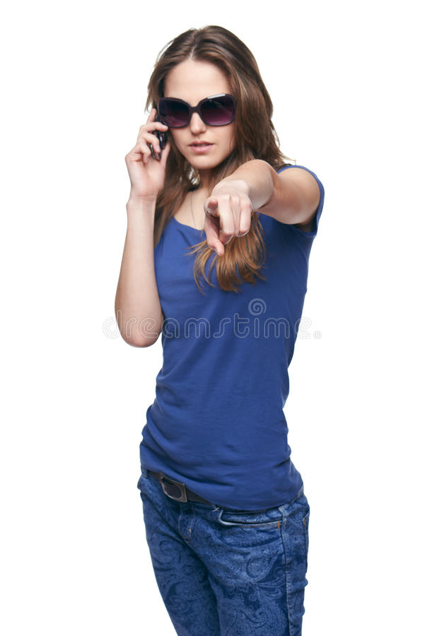 Woman pointing at camera while talking on cell phone. Young woman in sunglasses pointing at camera selecting you while talking on cell phone, focus on finger stock image